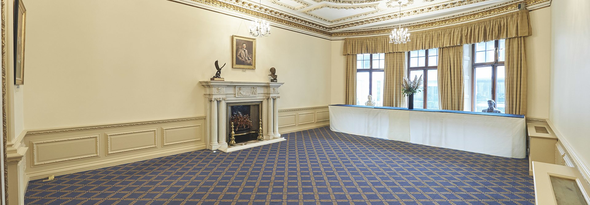 The Marshall of Cambridge room empty with fireplace, portraits and bay windows
