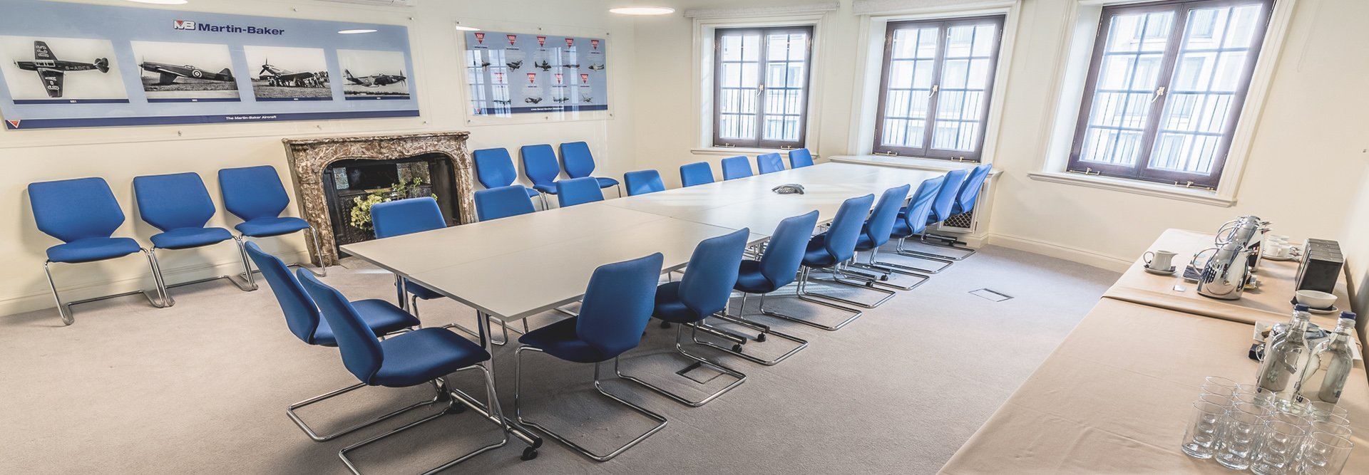 Room set up for meeting in boardroom style with blue chairs and refreshments